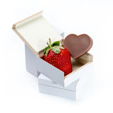 Strawberry and Heart-shaped chocolate in a box on white background Stock Photos