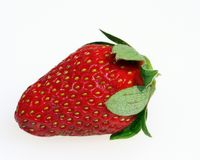 Strawberry heaven. A ripe strawberry close up, showing pips and leaves stock images