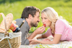 A strawberry for her. Young men feeding his girlfriend with stra Royalty Free Stock Images