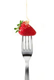 Strawberry with honey upon fork Royalty Free Stock Images
