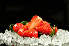 Strawberry on the ice on black background food postcard Royalty Free Stock Images
