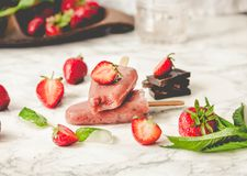 Strawberry ice cream with a banana and chocolate on a stick. Sum. Mer fresh dessert. Mint. Detox diet and summer food concept.Selective focus. Tone Royalty Free Stock Photo