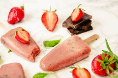 Strawberry ice cream with a banana and chocolate on a stick. Sum. Mer fresh dessert. Mint. Detox diet and summer food concept.Selective focus Stock Photography
