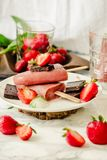 Strawberry ice cream with a banana and chocolate on a stick. Sum. Mer fresh dessert. Mint. Detox diet and summer food concept.Selective focus Royalty Free Stock Photos