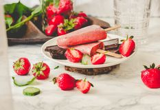 Strawberry ice cream with a banana and chocolate on a stick. Ton. Ing.Mint. Detox diet and summer food concept.Selective focus Royalty Free Stock Photography