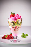 Strawberry ice cream. With berries, mint and kiwi slices stock photography