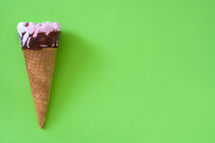 Strawberry ice cream cone on green background. Summer Strawberry ice cream cone on green background Stock Image