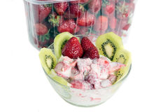 Strawberry and ice cream. Pistachio ice cream with kiwi segments against plastic capacity with strawberry Royalty Free Stock Images