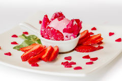 The strawberry ice cream for valentine. The strawberry ice cream serve with fresh strawberry and Rose petals on the white square plate decorate by the pink Stock Photo