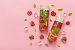 Strawberry infused water, cocktail, lemonade or tea. Summer iced cold drink with strawberry, lemon and mint  on pink  background. Flat lay. Top view royalty free stock image