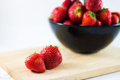 Strawberry isolated on white background. Strawberries fresh in a black cup on a wooden plate with a white background stock photos