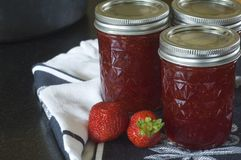Strawberry Jam. A young woman ladles hot strawberry jam into canning jars Royalty Free Stock Image