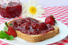 Strawberry jam. And bread on a plate Stock Images