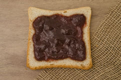 Strawberry jam on bread. On wood adn canvas Stock Photo