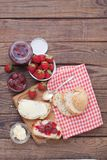 Strawberry jam, butter and bread on wooden table. Royalty Free Stock Photo