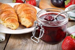 Strawberry jam and croissant on wooden table. Royalty Free Stock Photos
