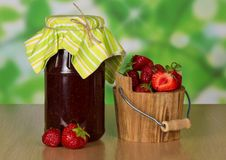 Strawberry jam and fresh berries in bucket. Bank with jam, a bucket with strawberry, and berries on a table Stock Image