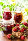 Strawberry jam and fresh strawberries. Still life with various types of strawberry jam and fresh strawberries Stock Image