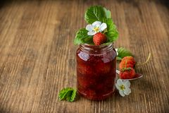 Strawberry jam in a glass jar with strawberries on Royalty Free Stock Photography