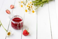 Strawberry jam in a glass jar on a table with chamomiles Royalty Free Stock Photos