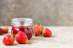 Strawberry jam in a glass jar on the table Stock Images