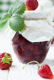 Strawberry jam in a jar on a white table Stock Photography