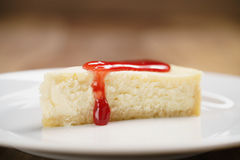 Strawberry jam pour on cheesecake on plate on wood table Royalty Free Stock Image