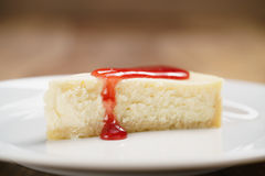 Strawberry jam pour on cheesecake on plate on wood table Stock Images