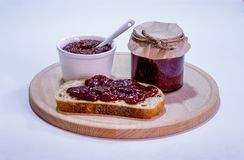 Strawberry jam on rustic bread on wooden plate. On white background Royalty Free Stock Photography