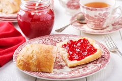 Strawberry jam spread on a slice of bread Stock Image