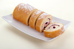 Strawberry jam swiss roll. Dessert on square plate , disposable paper tablecloth background Stock Photos