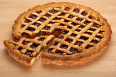 Strawberry Jam Tart. Homemade whole strawberry jam tart whit a slice cut out Royalty Free Stock Image