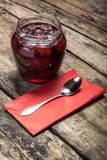 Strawberry jam with teaspoon served on wood background Royalty Free Stock Photography