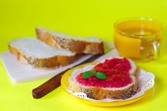 Strawberry jam on a white bread tea cup. Strawberry jam on a white bread decorated on   yellow background Stock Images