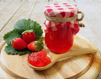 Strawberry jam. In a wooden spoon stock image