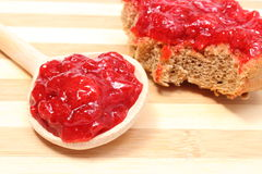 Strawberry jam on wooden spoon and whole wheat bread Royalty Free Stock Images