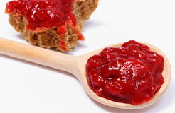 Strawberry jam on wooden spoon and whole wheat bread Stock Photo