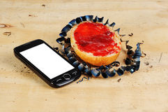 Strawberry jelly bread roll with metal cuttings and mobile phone on a bench Stock Photos