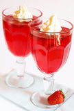 Strawberry jelly with cream. Strawberry jelly with fresh strawberry and cream in tall glass on light background Stock Image