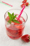 Strawberry juice in a crooked drinking glass Royalty Free Stock Photography