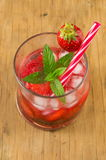 Strawberry juice in a crooked drinking glass Royalty Free Stock Image