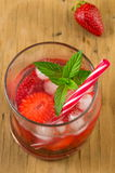 Strawberry juice in a crooked drinking glass Royalty Free Stock Photos