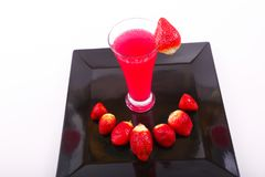 Strawberry juice with strawberries. Strawberry juice in glass with some strawberries on black dish over white background Royalty Free Stock Image