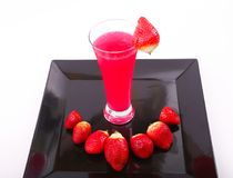 Strawberry juice with strawberries. Strawberry juice in glass with some strawberries on black dish over white background Royalty Free Stock Photo