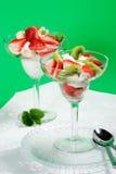 Strawberry and kiwi dessert in glass. Martini glass full of fresh kiwi, strawberries and cream with organic yogurt royalty free stock image