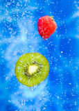 Strawberry and kiwi fruit in a water splash. Strawberry and kiwi fruit dropping ina splash of water drops royalty free stock photography