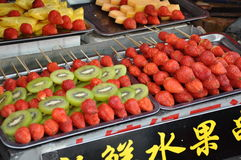 Strawberry and Kiwi sticks. Sticks of Kiwi and Strawberry at the food market in Beijing in China royalty free stock image