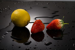 Strawberry and lemon on a black background Royalty Free Stock Photos