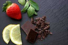 Strawberry, lemon slices, mint leaves and black chocolate on black slate background. Strawberry with some mint leaves, lemon slices and black chocolate on black Stock Photography