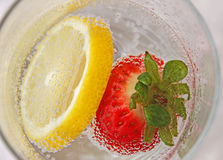Strawberry and lemon in a water glass. Slice of lemon and red strawberry in a glass of mineral water Royalty Free Stock Image